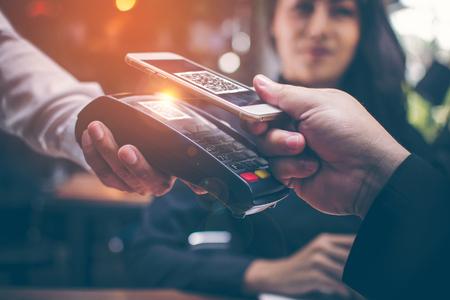 Le mani del giovane sono Smartphone per scansionare un QR CODE archiviato da un lettore di carte di credito per pagare cibo e bevande in ristoranti che hanno un'atmosfera romantica dalle ragazze asiatiche sedute insieme.