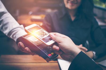 Las manos del hombre joven son un teléfono inteligente para escanear una presentación de CÓDIGO QR de un lector de tarjetas de crédito para pagar alimentos y bebidas en restaurantes que tienen un ambiente romántico por las chicas asiáticas que están sentadas juntas.
