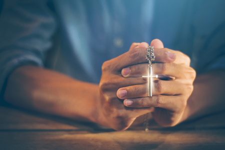 Closeup picture of a young Christian. He clasped hands and prayed God to bless the crucifix pendant, the symbol of the crucified Jesus by faith in Christ within the Catholic Church with copy space. Standard-Bild - 110708166