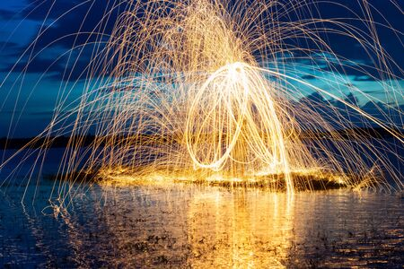 Image playing fireworks by rotating the wave shape of the lines, sparks to light. Amazing Fire Dance in the middle basin slope and beautiful reflection. Imagens