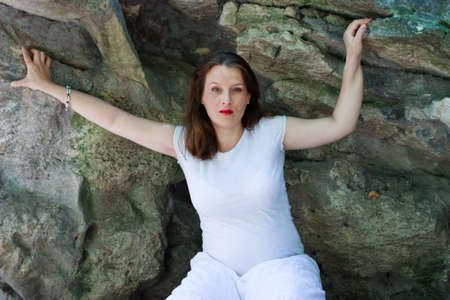 Beautiful young pregnant girl dressed in white, with stones in the background photo