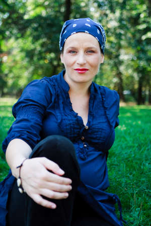 Green-eyed beautiful young woman dressed in blue and with a bandanna in nature photo