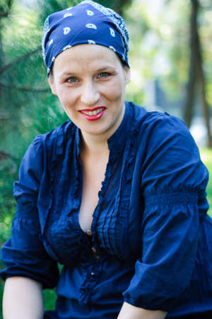 Green-eyed beautiful young woman dressed in blue and with a bandanna in nature smiling photo