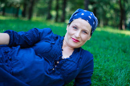 Green-eyed beautiful young pregnant woman dressed in blue and with a bandanna in nature couched photo