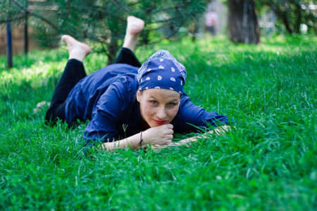 Green-eyed beautiful young woman dressed in blue and with a bandanna lying in the grass photo