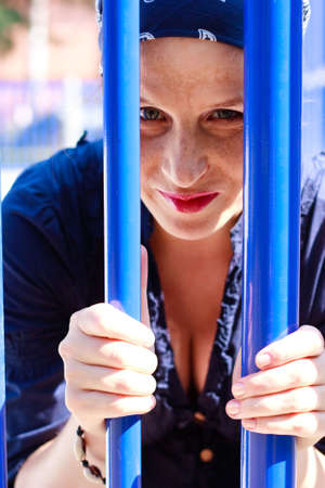 Green-eyed beautiful young woman with blue bars photo