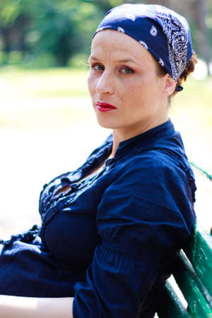 Green-eyed beautiful pregnant young woman dressed in blue resting on a bench photo