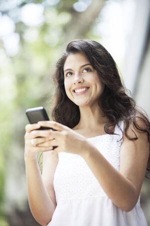 cel: Bella donna latina sorridente con Cel Phone Archivio Fotografico
