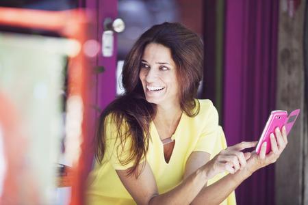 cel: Bella donna matura sorridente con Cel Phone Archivio Fotografico