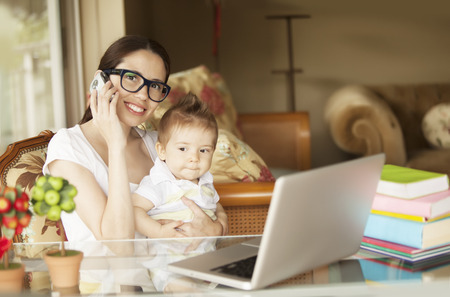12 18 months: Woman Working at Home with Baby Stock Photo