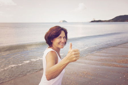 Happy woman running on the beach photo