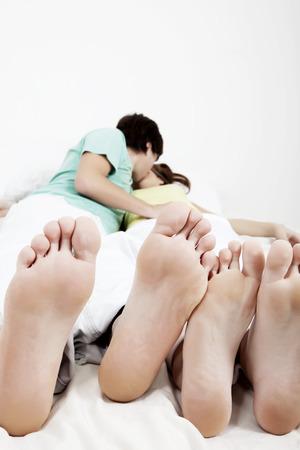 pareja adolescente: Feliz pareja joven en la cama, bes�ndose, GDL en los pies