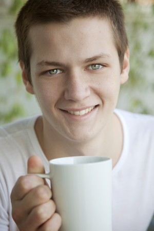 Happy young man having coffee photo