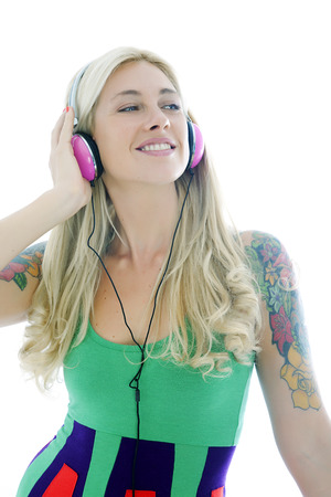 tattoed: Blonde tattooed woman dancing with headphones Stock Photo