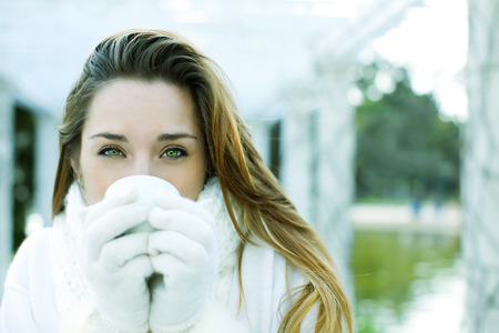 Happy young woman having tea, winter clothes photo