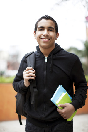 13 14 years: Happy african american teenage boy with books and backpack Stock Photo