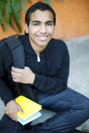13 14 years: Happy african american teenage boy with book and backpack