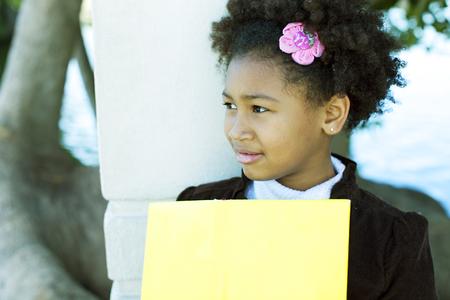 niños africanos: Niña afroamericana feliz con el libro Foto de archivo