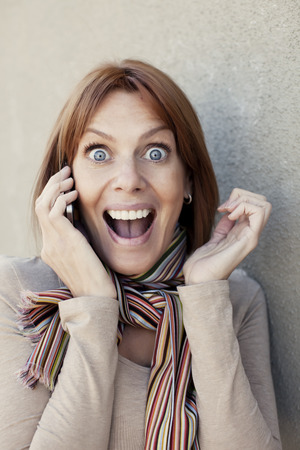 40 44 years: Happy adult woman surprised on the phone
