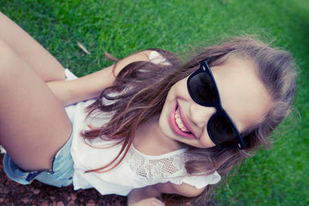 lying on back: Happy little girl wearing sunglasses, lying on the grass