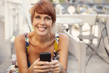 40 44 years: Happy adult woman with mobile phone, sending a text message