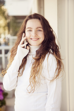 12 13 years: Happy girl on the phone, smiling Stock Photo