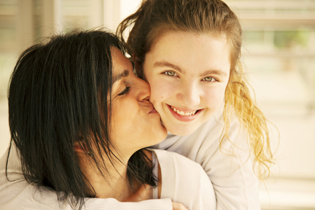 hispanic kids: Mother kissing daughter