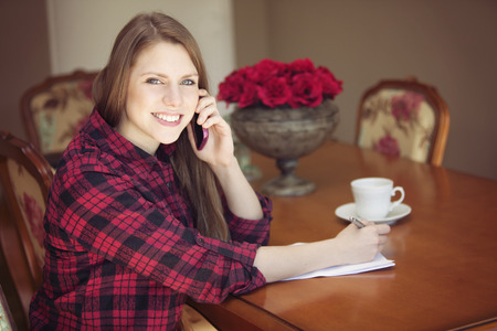 hi back: Happy young woman working at home, talking on the phone