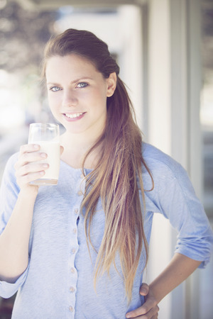woman drinking milk: Happy young woman drinking milk Stock Photo