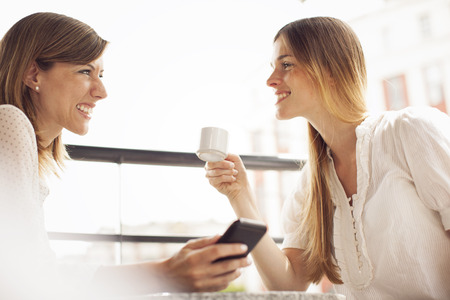 two people talking: Amigos felices mujeres tomando un caf� y hablando al aire libre