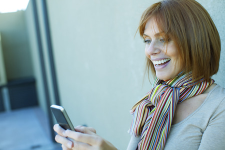 40 44 years: Happy adult woman with mobile phone, sending text message Stock Photo