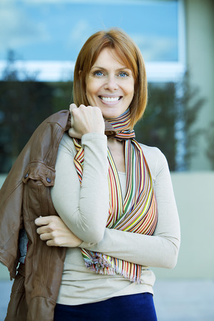 40 44 years: Happy audlt woman smiling outdoors with jacket Stock Photo