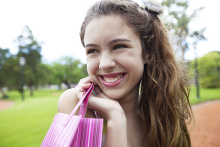 13 14 years: Happy little girl with shopping bag, smiling