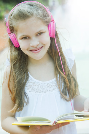 8   9 years: Happy little girl with books and headphones outdoors