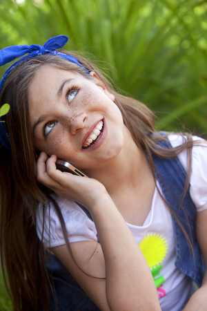 cel: Happy little girl on the phone Stock Photo