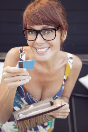 40 44 years: Adult beautiful woman with glasses, paying with credit card, smiling