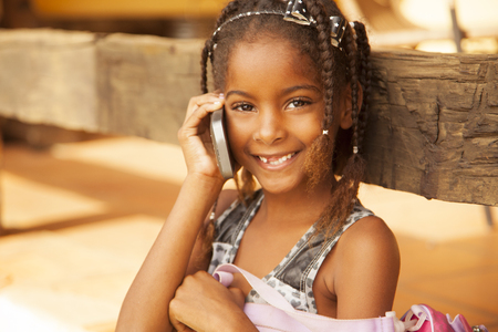 niños pobres: Niña afroamericana feliz en el teléfono, hablar