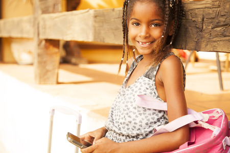 brazilian ethnicity: Happy african american girl with mobile phone, sending text message Stock Photo