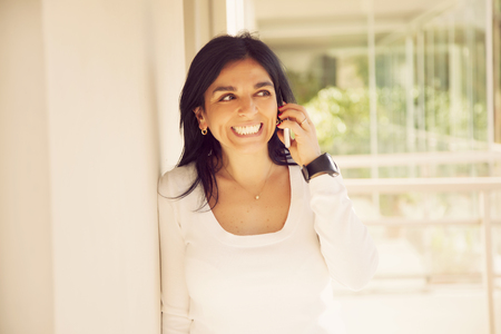 cel: Happy adult latin woman on the phone, smiling