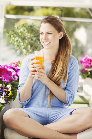 Happy woman drinking orange juice in the morning photo