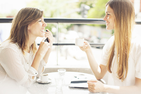 Talking on the phone: Happy friends having coffee and talking outdoors Stock Photo