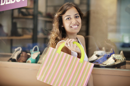 buying: Happy young woman buying shoes Stock Photo