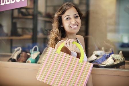 buying shoes: Mujer joven feliz comprar zapatos Foto de archivo