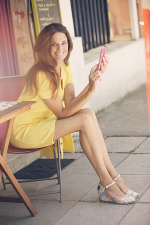 40 44 years: Adult woman with mobile phone, smiling outdoors