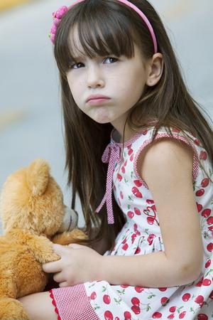 angry teddy: Little girl sulking with teddy bear Stock Photo