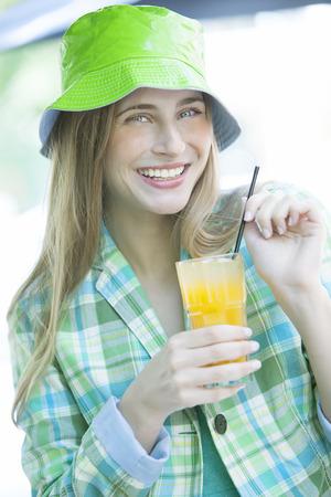 Happy woman drinking orange juice photo