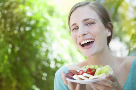 fruit salad: Happy woman eating fruit salad