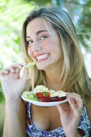 woman eating fruit: Happy woman eating fruit salad
