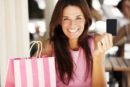 Happy adult woman paying with credit card