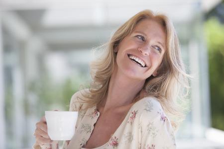 femmes souriantes: Bonne thé potable de femme mûre Banque d'images